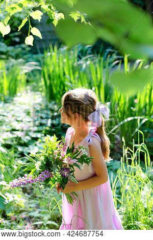 Portrait Of A Six Year Old Girl With Bouquet Of Flowers In The Forest.