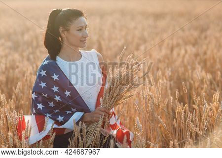 Woman With American Usa Flag And With A Sheaf Of Ears In Wheat Field At Sunset. 4th Of July. Indepen