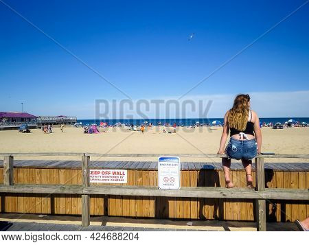 Pt Pleasant, Nj - Usa - June 23, 2021:  A Girl Takes In The Beach Scene While Sitting On The Boardwa