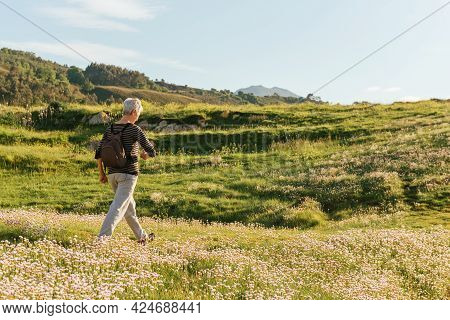 Senior Woman Walking Energetically Through A Flower Field As A Healthy Lifestyle. Seniors And Exerci