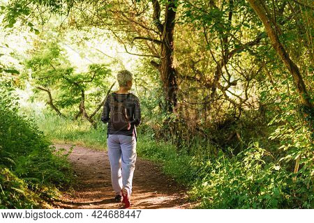 Older Woman With Gray Hair On A Hike In The Woods. Old Age And Healthy Lifestyle.
