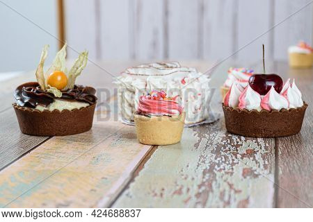 Mini Sablée Pastry Pies With Whipped Cream Topping, Alongside Mini Tarts With Cherries And Physalis.