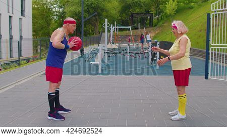 Active Senior Old Couple Basketball Team Man And Woman Playing Game With Ball, Pass To Each Other At