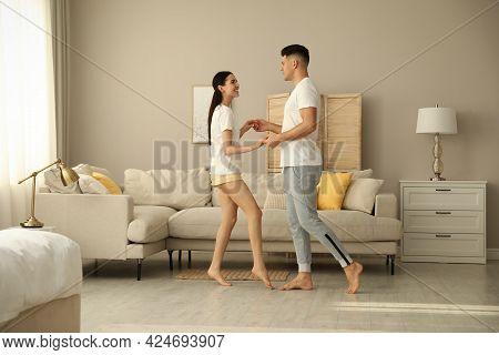 Happy Couple In Pyjamas Dancing At Home