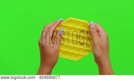 Close-up Of Girl Hands Squeezing Presses Colorful Anti-stress Touch Screen Push Pop It Toy. Sensory