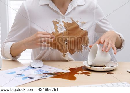 Woman In Dirty Shirt At Wooden Desk With Coffee Spill, Closeup