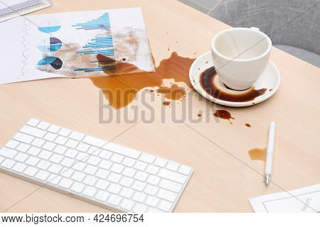 Cup With Saucer And Coffee Spill On Wooden Office Desk