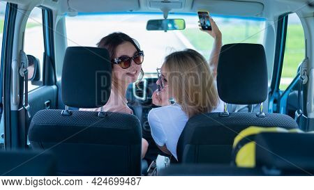 Two Friends Go On A Trip. Rear View From The Trunk Of A Caucasian Woman Driving In A Car And Taking