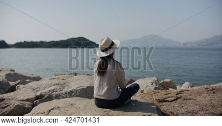 Woman sit on seaside and look at the scenery view