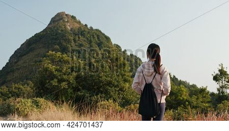 Woman look at the mountain and prepare to hike