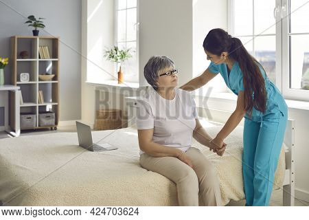 Home Care Nurse Or Caregiver Supports And Assists Senior Woman With All Her Daily Needs