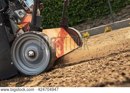 Lawn Aerator In Action. Close Up Photo. Gardening And Landscaping Theme.