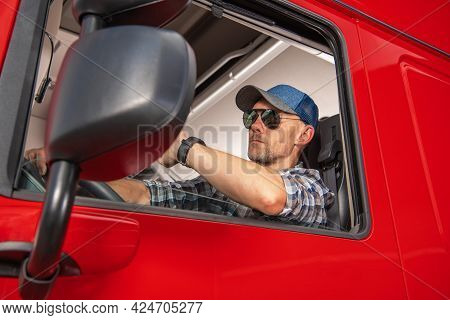 Professional Caucasian Semi Truck Driver In His 40s Behind The Steering Wheel Of His Tractor Truck.