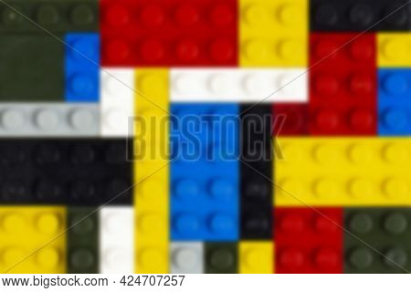 Blurred Background Of Colored Parts Of A Children Constructor As A Background Or Backdrop. Place For
