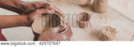 Partial View Of Young African American Couple Sculpting Clay Pot With Holding Hands Together In Pott