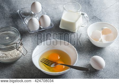 Raw Ingredients For Making An Omelet. Eggs And Flour On A Gray Background. Cooking Concept