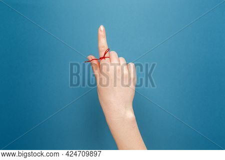 Mental Health. Close-up Of A Female's Hand With A Red Thread Tied On The Finger, As A Reminder. Flat