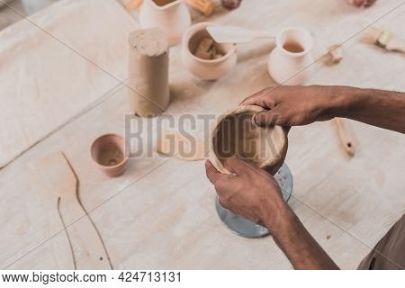 High Angle View Of Young African American Woman Sculpting Clay Pot With Spatula In Pottery