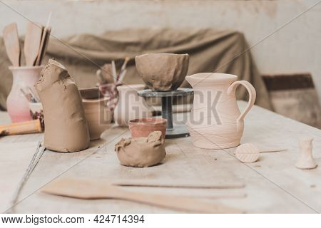 Handmade Pots, Sculpted Clay Bowl And Pottery Equipment On Wooden Table