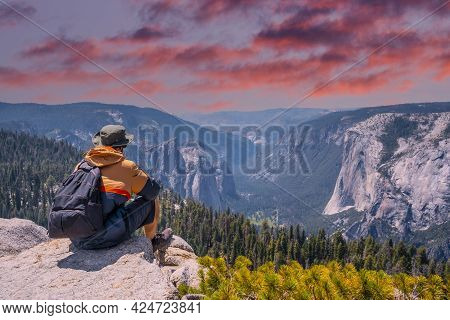 A Young Winged Seated Taft Point Looking At Yosemite National Park And El Capitan In Sunset. United