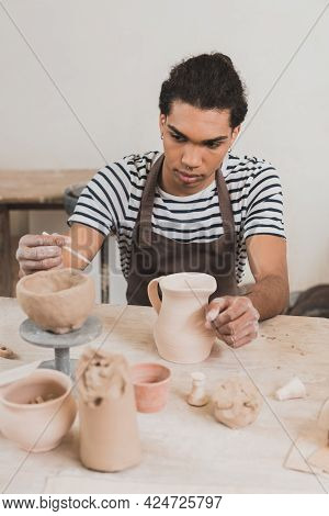 Serious Young African American Man Sculpting Clay Pot And Stick On Table With Equipment In Pottery