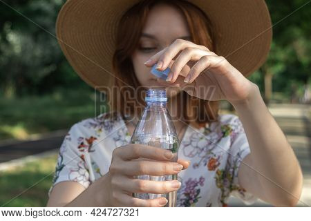 The Girl Opens A Bottle Of Water. Pure Drinking Water In A Plastic Bottle. Opening Bottle Of Water C