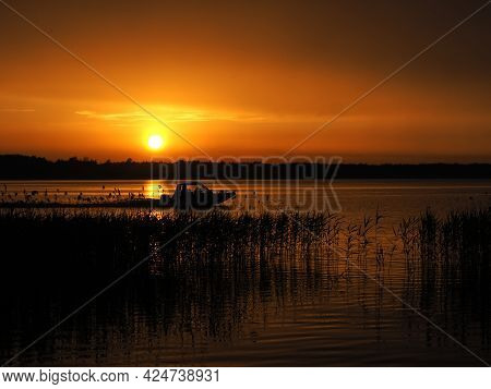 Motorboat And Sunset. Vacation Time And Travel. Speed and Wind. Sultry Evening And Lake