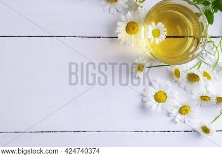 Close-up Top View Of A Cup Of Chamomile Tea And Flowers. Alternative And Traditional Medicine. Herba