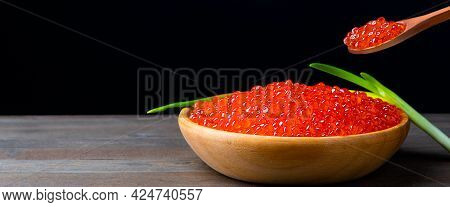 Red Caviar In A Wooden Cup On A Black Background With A Spoon And Green Onions. A Large Pile Of Brig