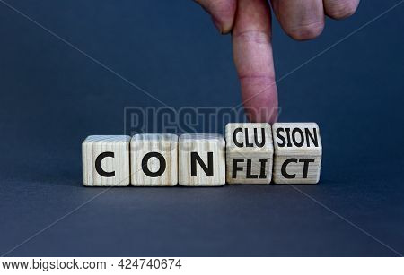 Conflict Or Conclusion Symbol. Businessman Turns Wooden Cubes, Changes The Word 'conflict' To 'concl
