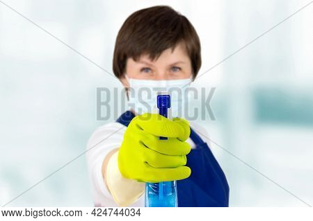 The Concept Of Disinfection And Cleaning. Cleaner Woman Hold Cleaning Spray As A Pistol, With Mask.