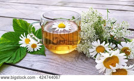 Chamomile Tea In A Glass Cup. A Transparent Cup With A Chamomile Drink Stands On A Wooden Background
