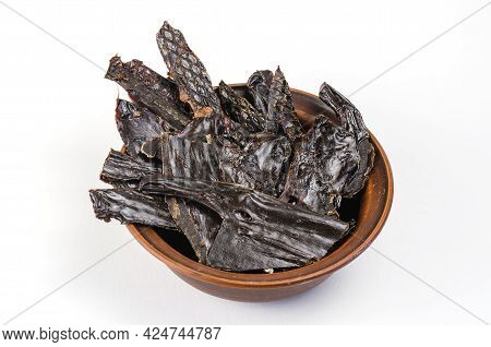 Dried Dog Treats In A Brown Clay Bowl On A White Background. Thin Slices Of Dehydrated Beef Liver. T