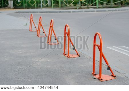Parking Barriers In A Row. Five Orange Metal Folding Barriers On The Pavement. Daytime.