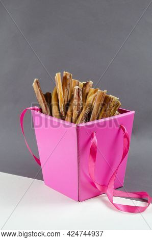 Pretty Pink Gift Box With Pet Treats. Open Box Full Of Bully Sticks For Dogs On Gray And White Backg