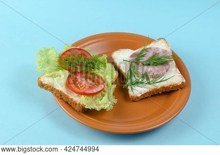 Ham Sandwich And Brown Plate On A Light Blue Background. Ready-to-eat Food. Ham, Tomato, Lettuce, Di