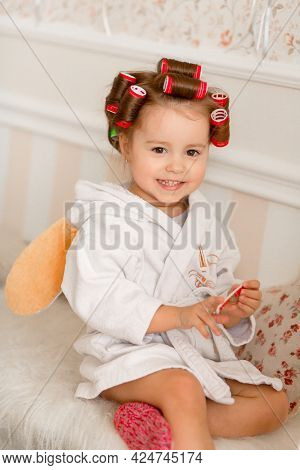 Adorable Little Girl With Curlers Paints Her Fingernails. Copies Mom's Behavior. Young Fashionista.