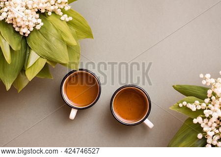 Two Mugs With Tea And Bouquets Of Lilies Of The Valley On A Green Background. Pause For Rest, Slow L