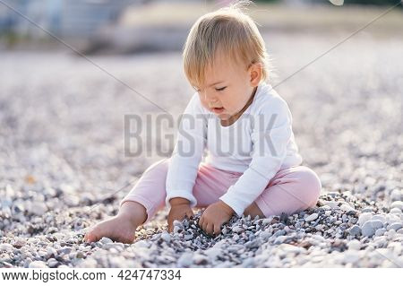 Kid Sits On A Pebble Beach And Digs Small Pebbles