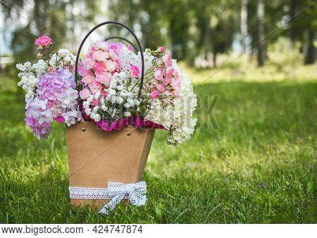 Bouquet Of Phlox Flowers In A Design Paper Cardboard Box On A Background Of Park Grass.