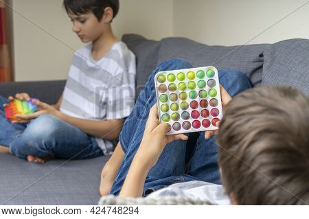 Teenage Boys Playing With Rainbow Pop-it Fidget Toys At Home. Push Pop-it Fidgeting Game Helps Relie
