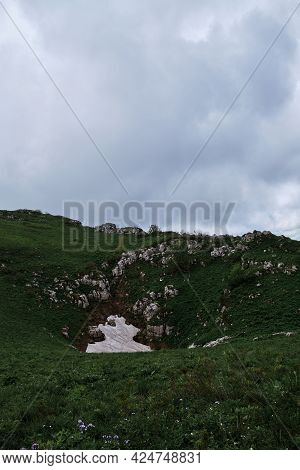 A Little Snow In Summer In Mountains. In June, Not All Snow In Mountains Has Yet Melted And Snow Blo
