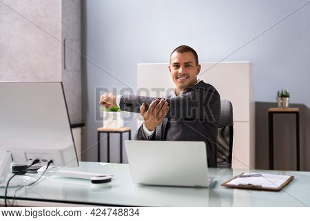 Man Doing Stretching Exercise At Desk Working On Computer