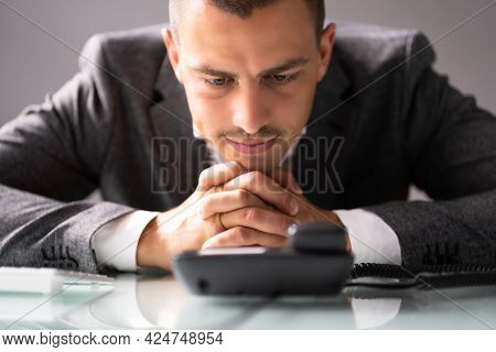 Waiting For Phone Call On Office Landline At Desk
