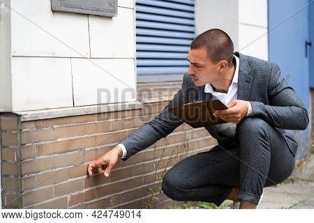 Real Estate Property Appraisal. Man Inspecting House