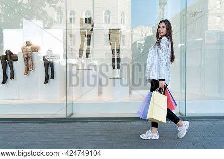 Young Girl While Shopping. Woman With Colorful Packets Walks Past Shop Windows.