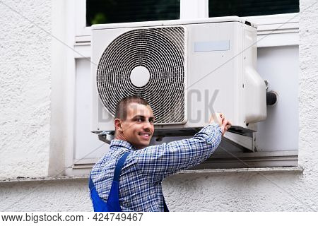 Technician Cleaning And Repairing Air Condition Appliance. Ac Unit Maintenance