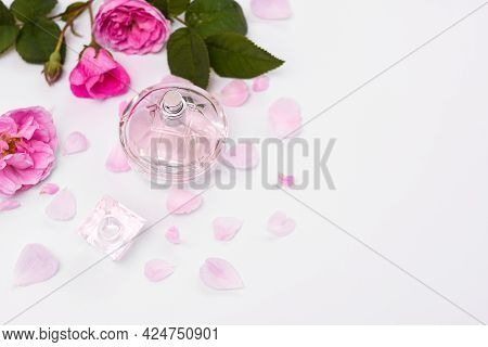 Eau De Toilette With A Floral Fragrance. Women's Perfume In A Glass Bottle With Pink Flowers On A Wh