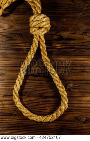 Deadly Loop Of Rope On A Wooden Background. Concept Of Death Penalty Or Suicide