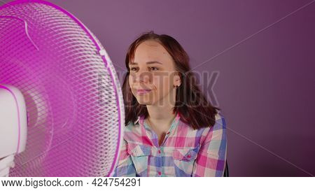 Close Up Of Young Woman Sitting On Chair In Front Of Fan On Purple Background. Happy Brunette Enjoyi